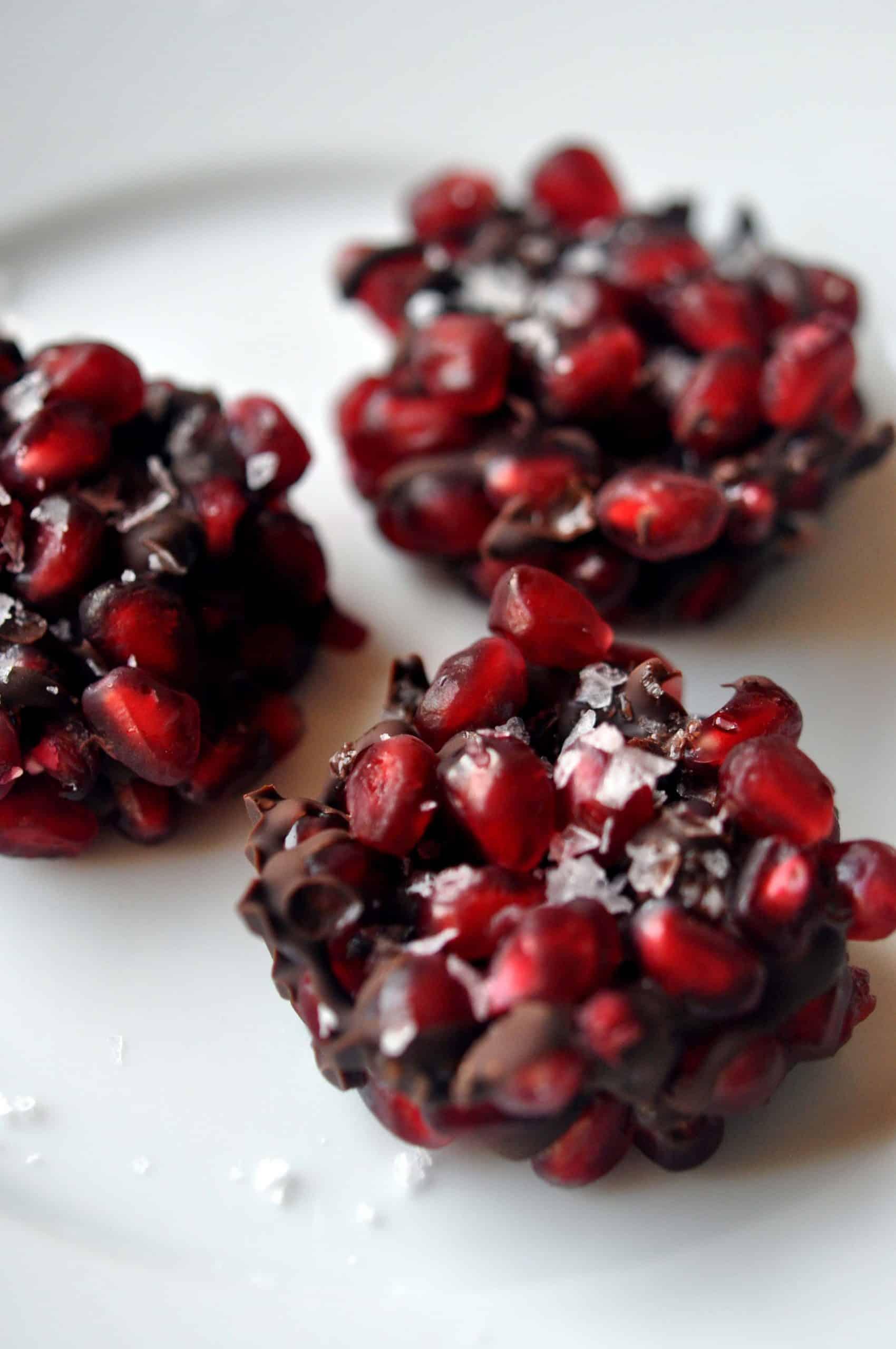 three pomegranate dark chocolate bites on a white background