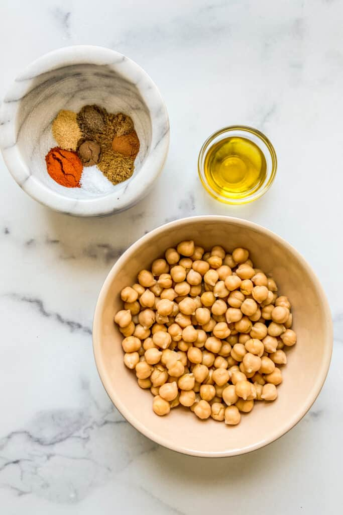 Bowls of tagine spices, chickpeas, and olive oil.