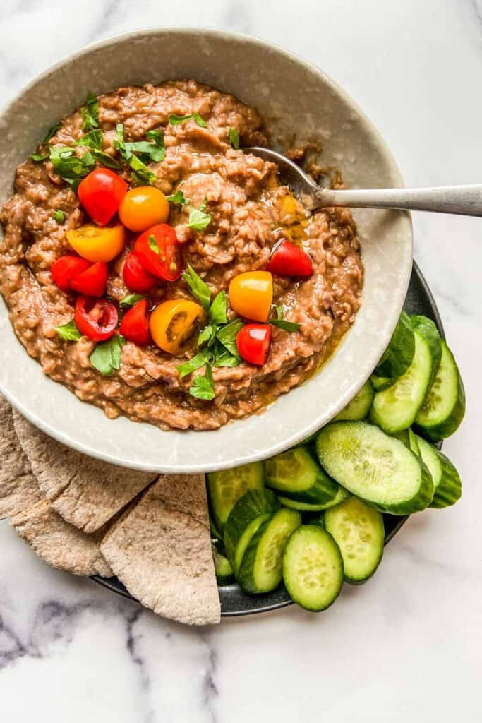 A bowl of ful medames topped with tomatoes and parsley, next to cut pita bread and sliced cucumbers.