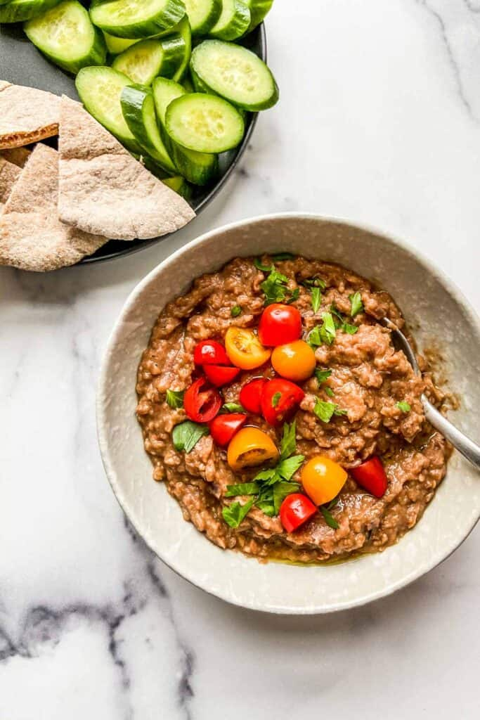An overhead shot of a bowl of foul medames served alongside pita and cut cucumbers.