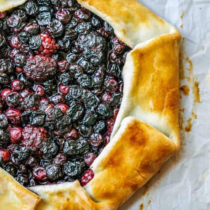 A blueberry blackberry galette on a parchment paper.