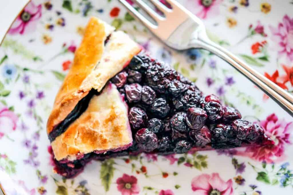 A slice of blueberry blackberry galette on a flowered plate.
