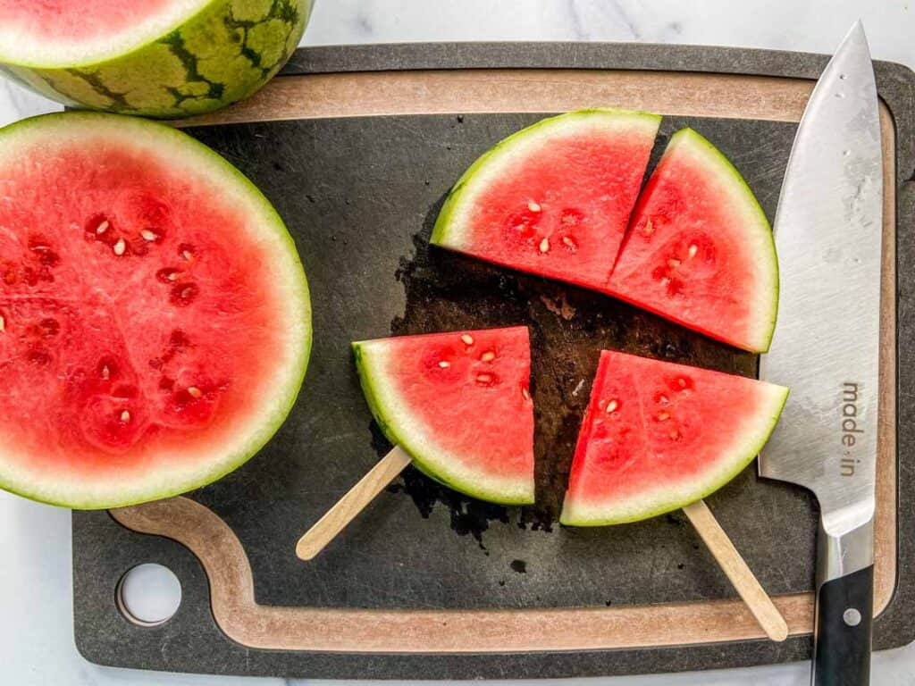 Sliced watermelon with popsicle sticks pushed into them.