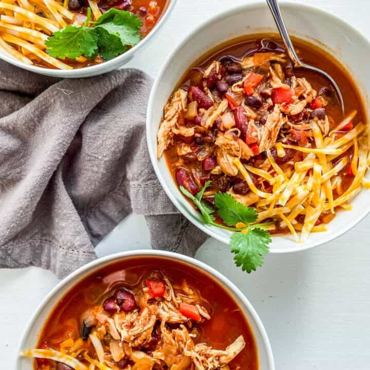 three bowls of chicken chili garnished with cheese and cilantro