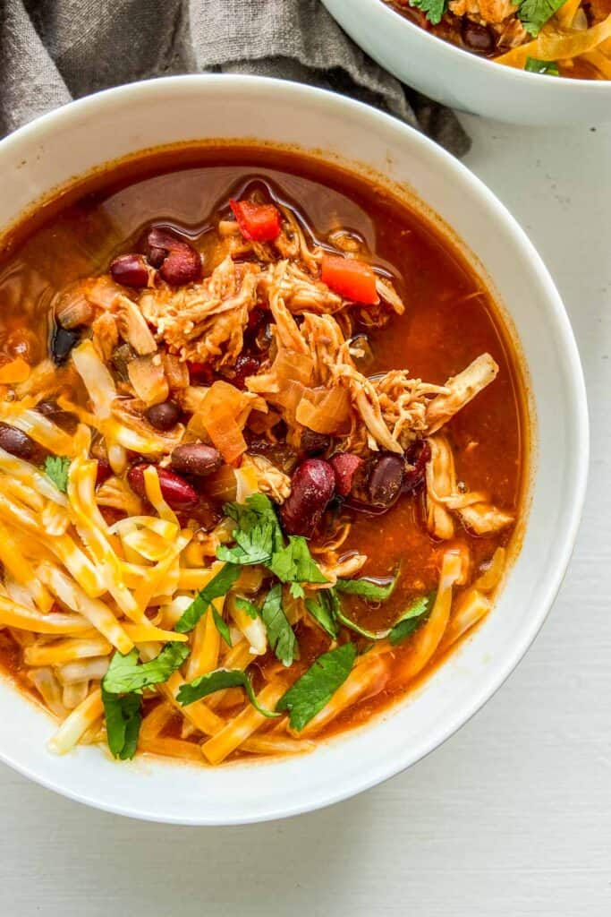 a closeup of a bowl of chicken chili with cheese and cilantro garnish
