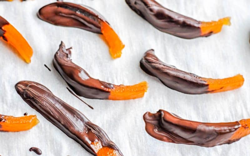 dark chocolate covered clementine peels on parchment