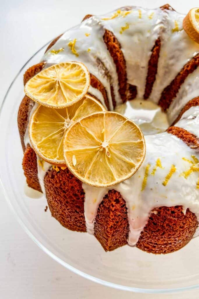 orange bundt cake with glaze on a glass cake plate