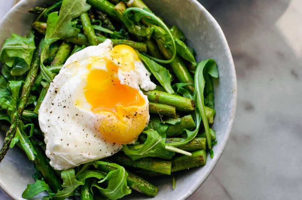 breakfast bowl with arugula, asparagus, and poached egg
