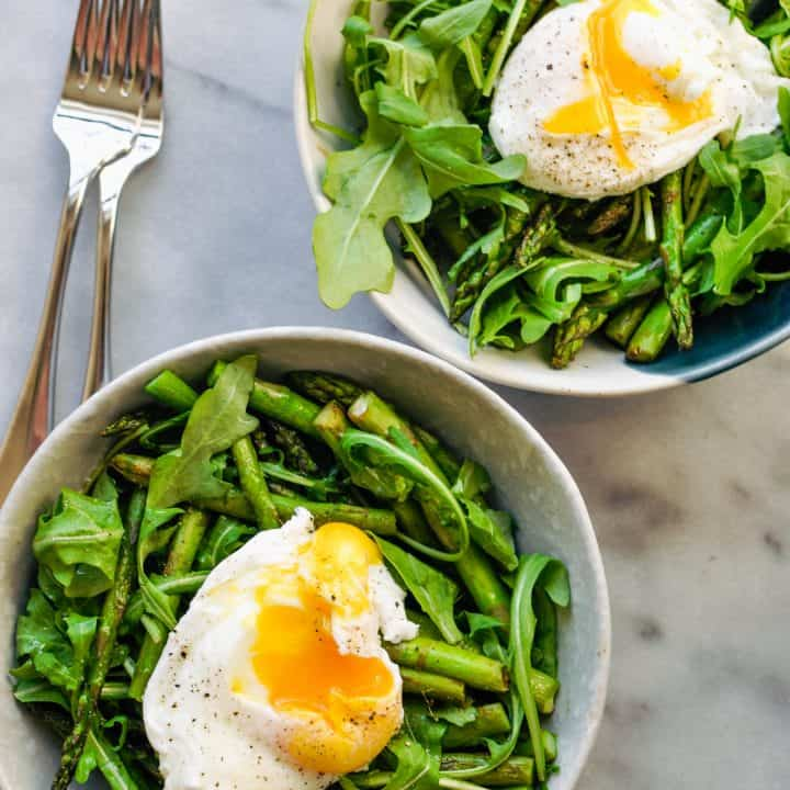arugula and asparagus in a bowl with poached egg