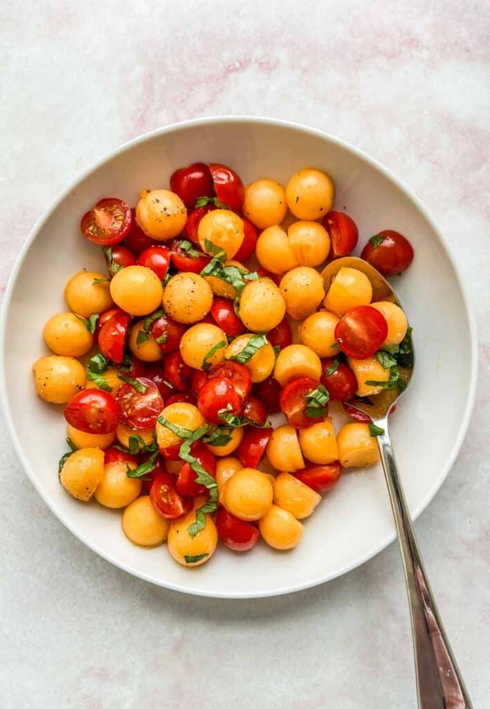 cherry tomato and cantaloupe salad in a white serving bowl with a spoon