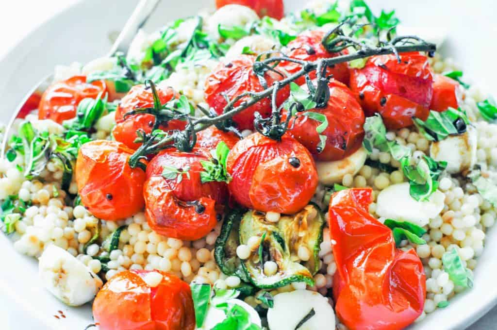tomatoes on top of israeli couscous salad