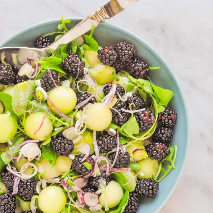 honeydew salad with blackberries in a blue serving bowl