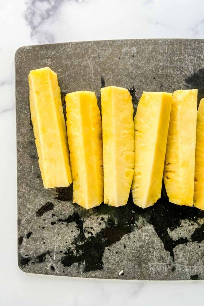 Spears of pineapple on a black cutting board.