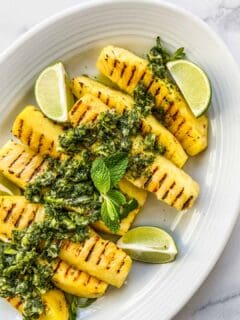 An overhead shot of grilled pineapple with lime mint sauce on a white serving dish.