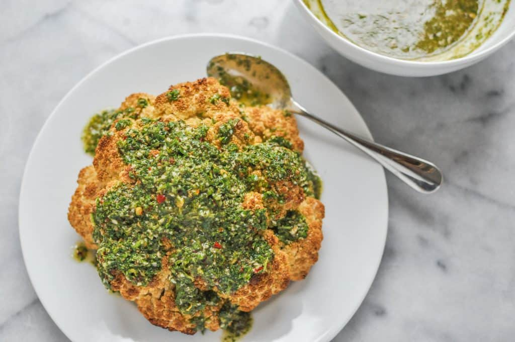 roasted head of cauliflower drizzled with chimichurri sauce