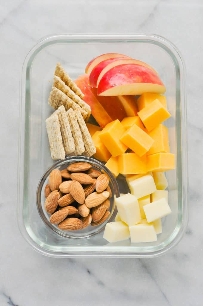 road trip snacks - cheese, apple, almonds, and crackers in a glass container