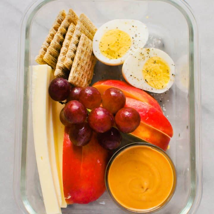 egg, grapes, apple, peanut butter, and crackers in a glass container