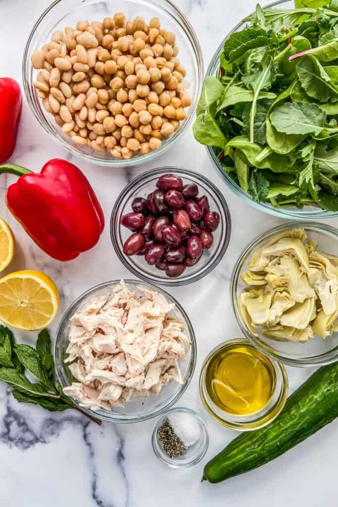 Ingredients for a chicken salad on a marble background.