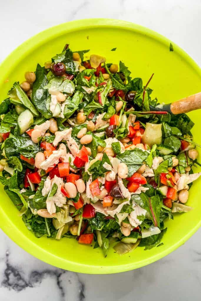 An overhead shot of a green mixing bowl with chicken salad.