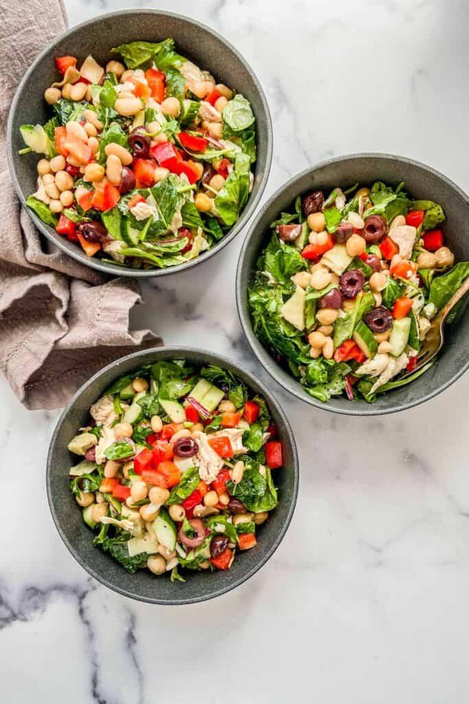 An overhead shot of three bowls of Mediterranean chicken salad.