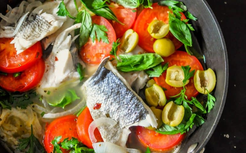 poached sea bass in a pan