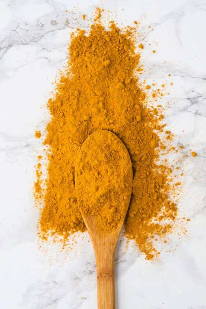 turmeric spice on a wooden spoon