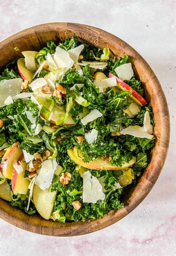 brussels sprouts kale and apple salad in a wooden bowl