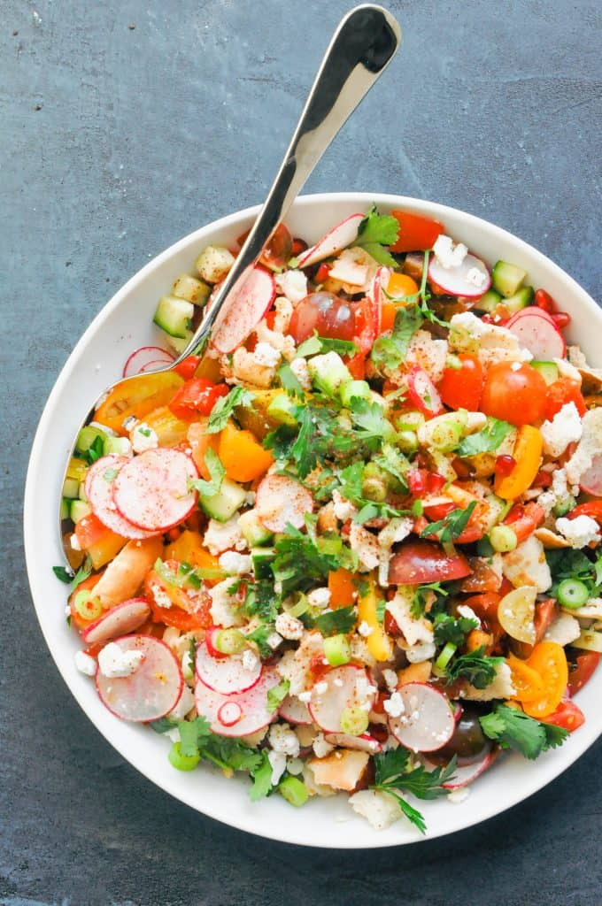 fattoush salad in a large serving bowl with a serving spoon