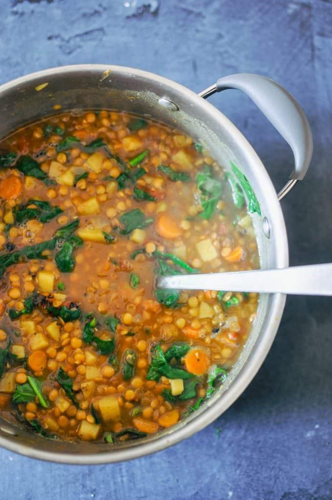 lentil soup in a large pot with a ladle