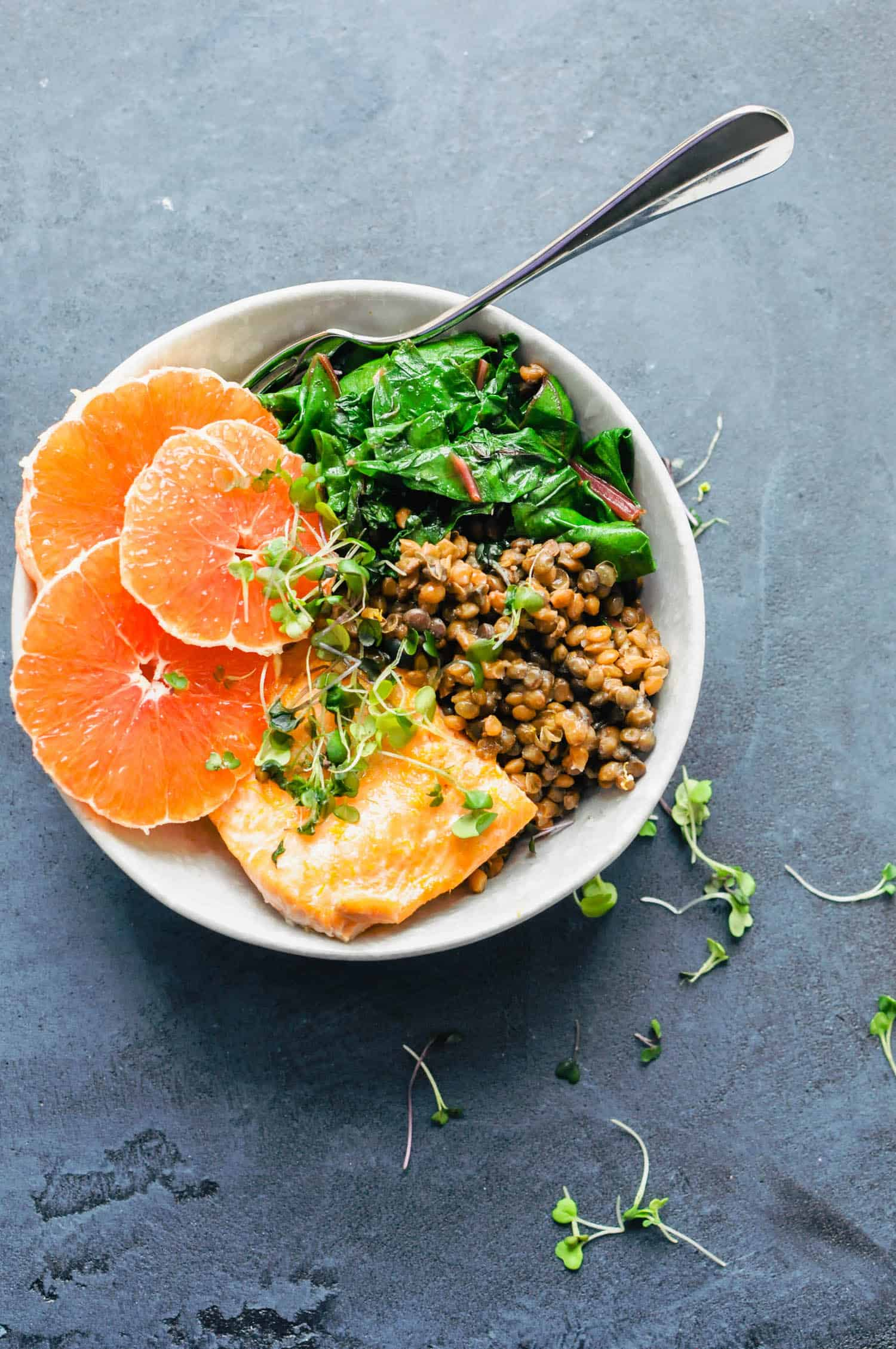 oranges, salmon, greens, lentils in a bowl