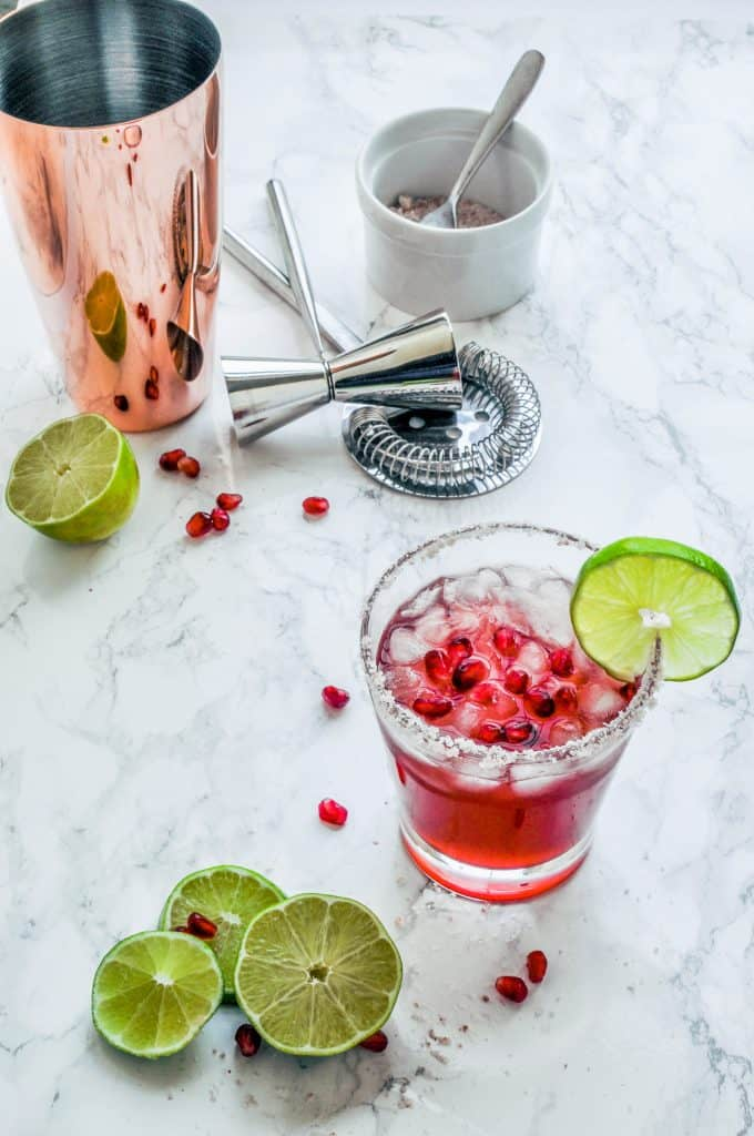 pomegranate margarita in glass with cocktail shaker