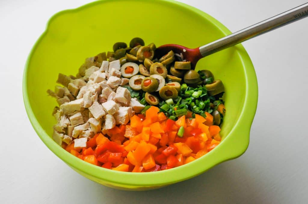 chicken orzo salad ingredients in a mixing bowl with a spoon