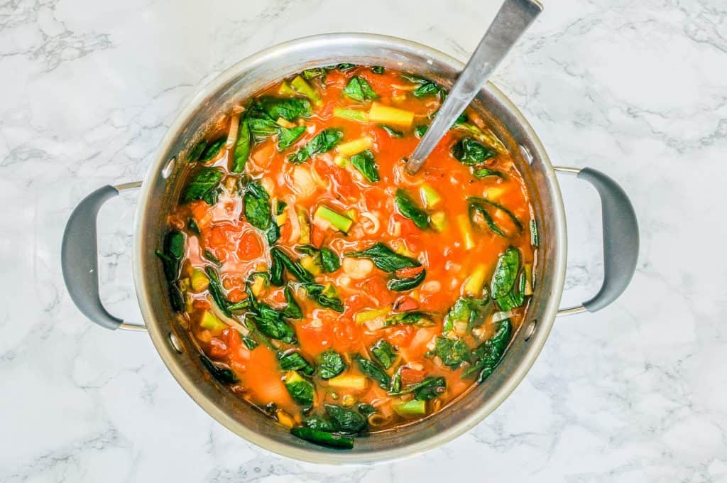 spring minestrone soup in a large pot with a silver ladle