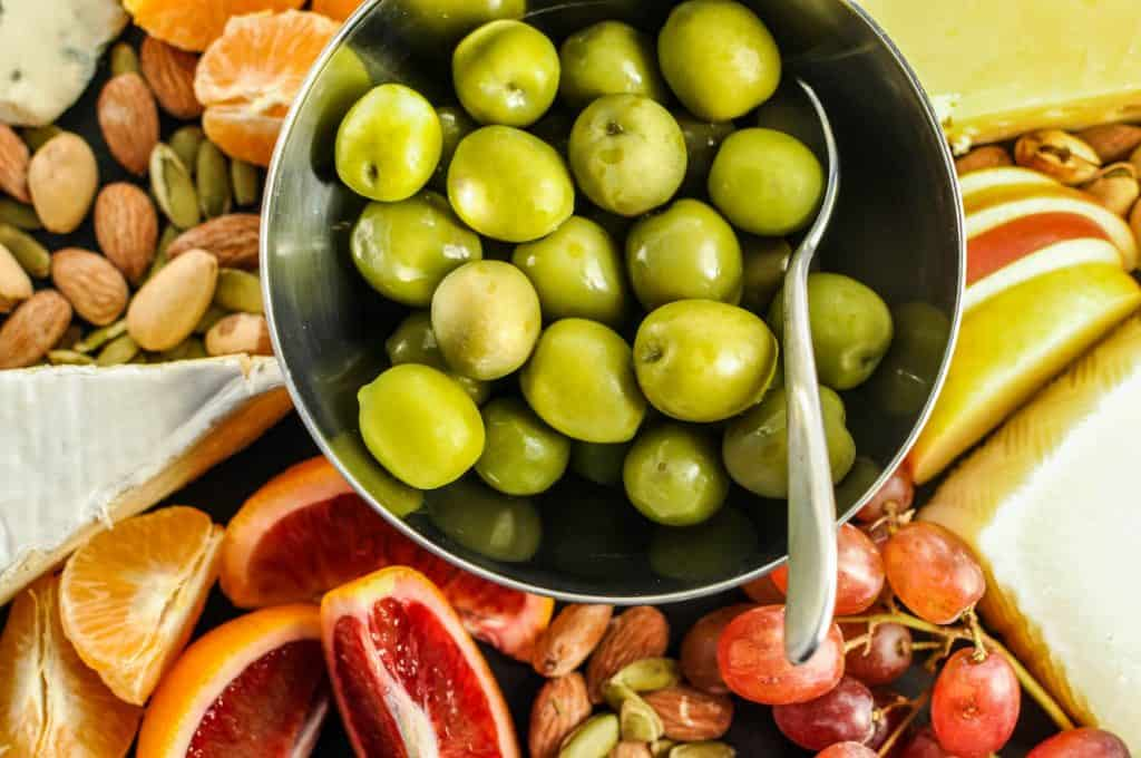 closeup of green olives on appetizer board