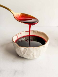 Pomegranate molasses dripping from a spoon into a small bowl.