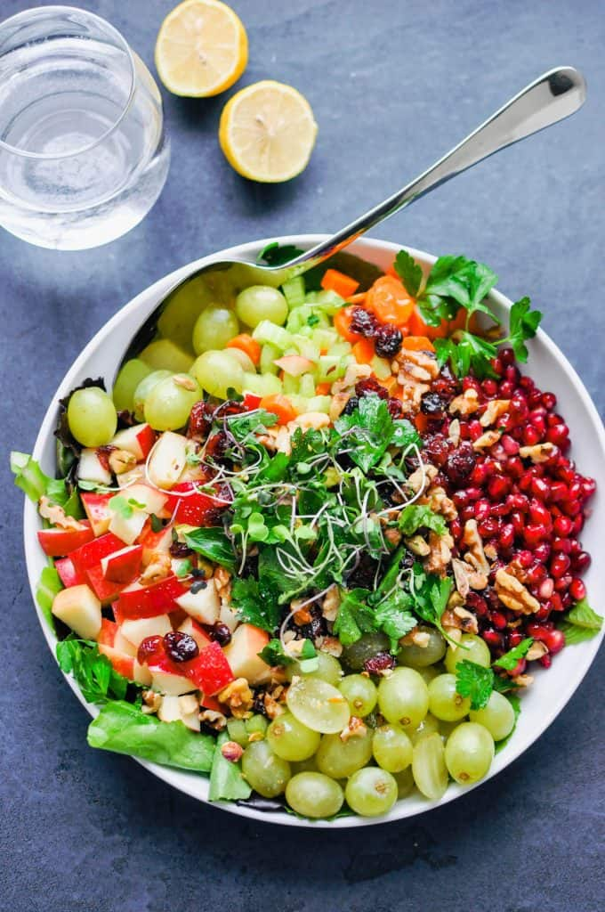 grapes, apples, pomegranate, and microgreens in a bowl