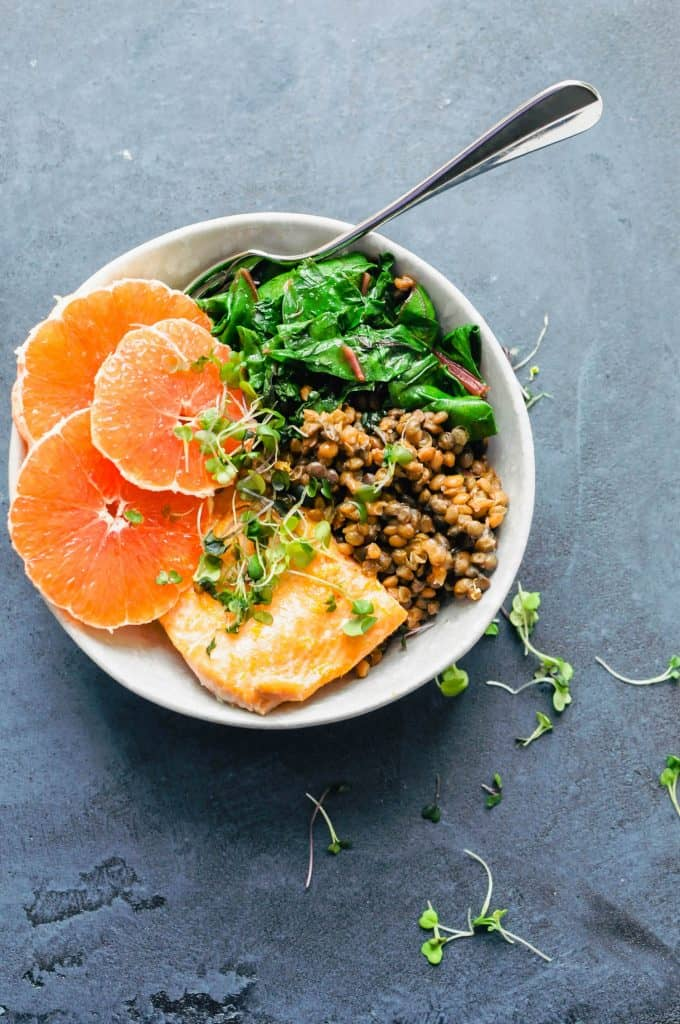 oranges, salmon, lentils, and greens in a bowl