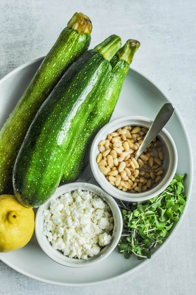 zucchini, lemon, pine nuts, and feta in a bowl