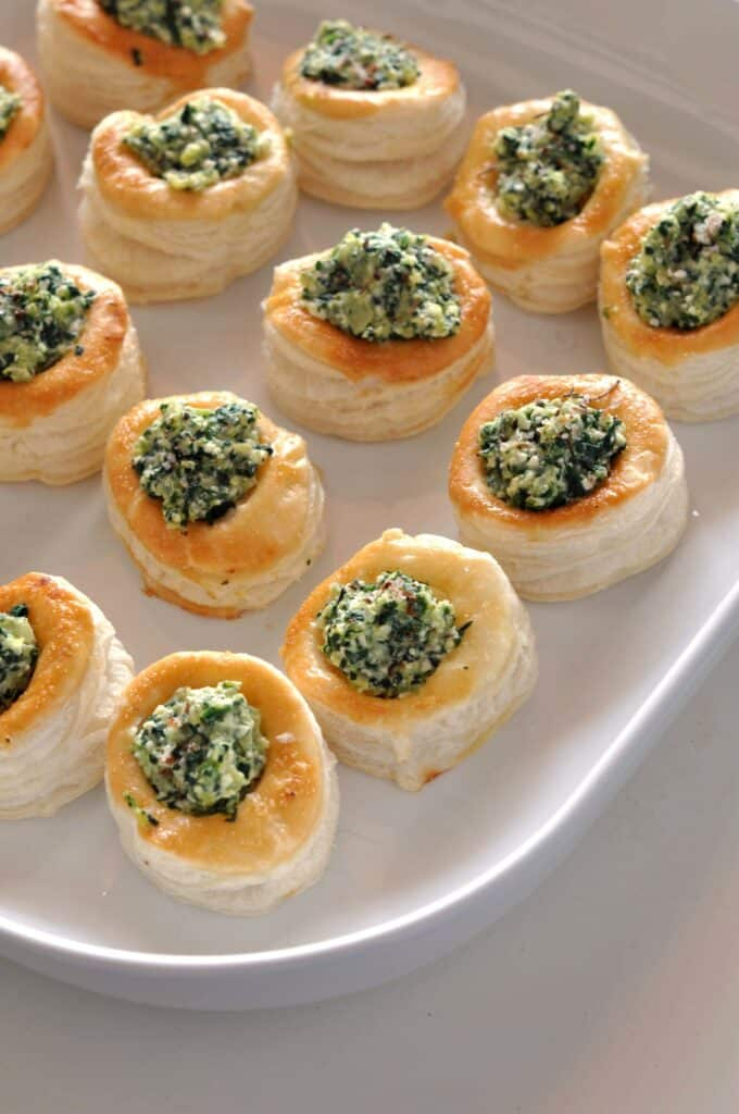 Spinach and feta puff pastry bites lined up on a serving plate.
