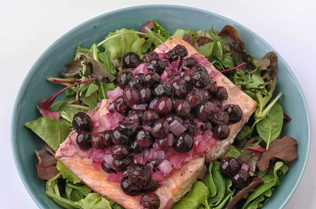 salmon and blueberries on a plate with greens