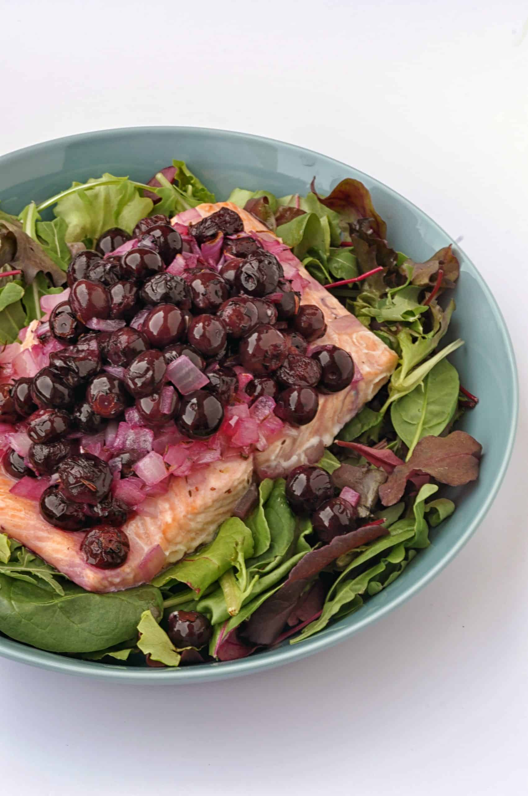 salmon with blueberries on a plate with greens
