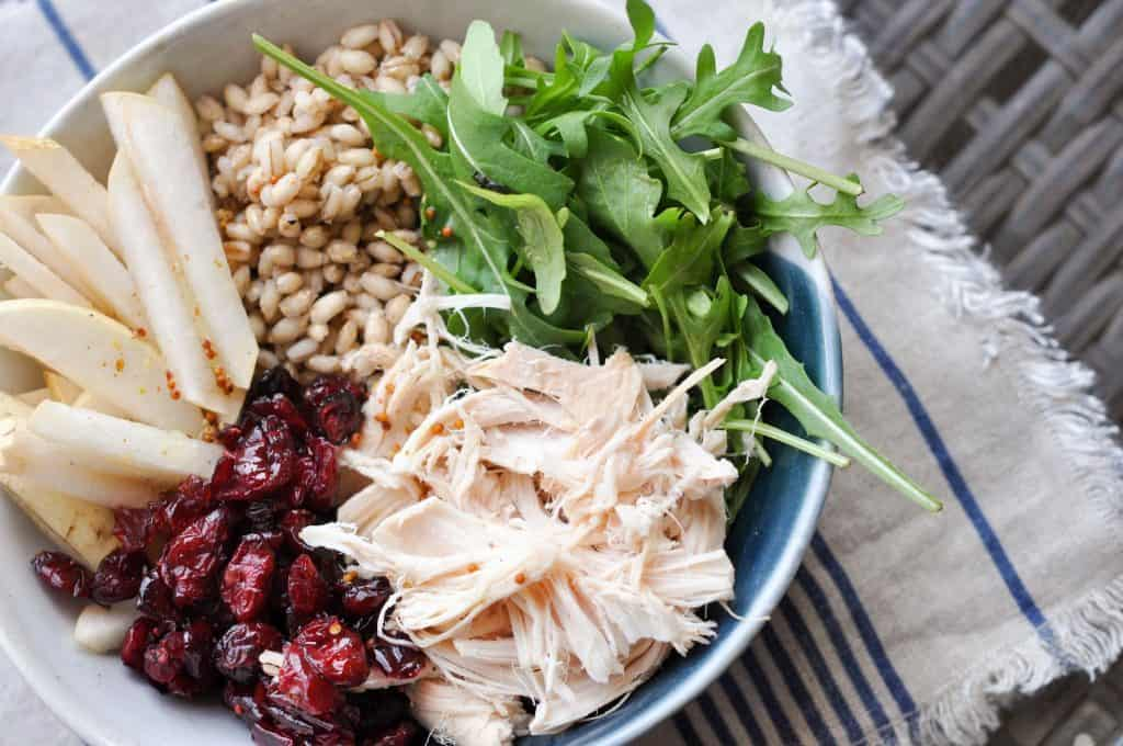 chicken, cranberries, bulgur, greens, and fruit in a bowl