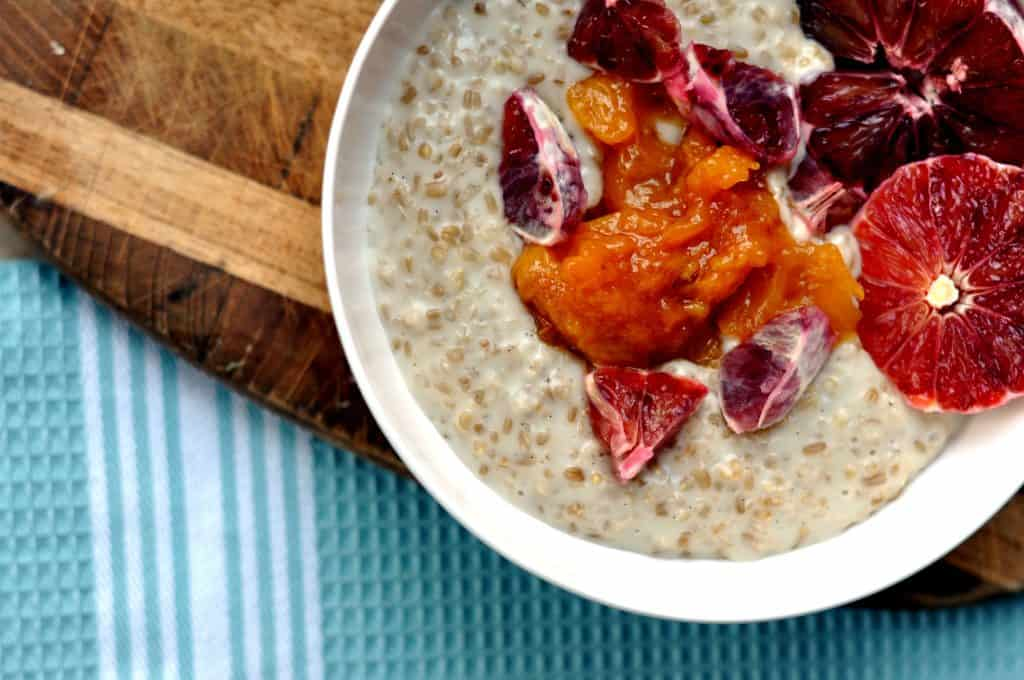 almond milk steel cut oats in a bowl topped with peach compote and blood oranges