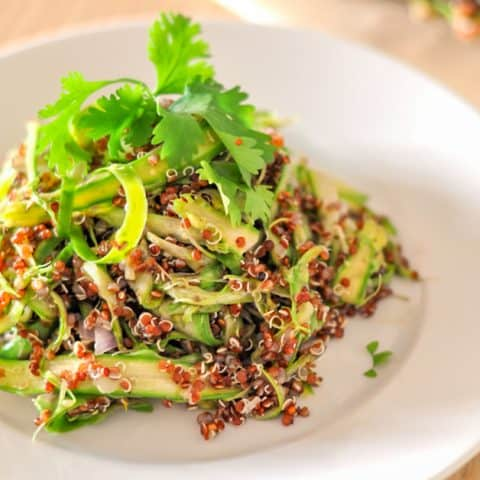 shaved asparagus with quinoa on a white plate