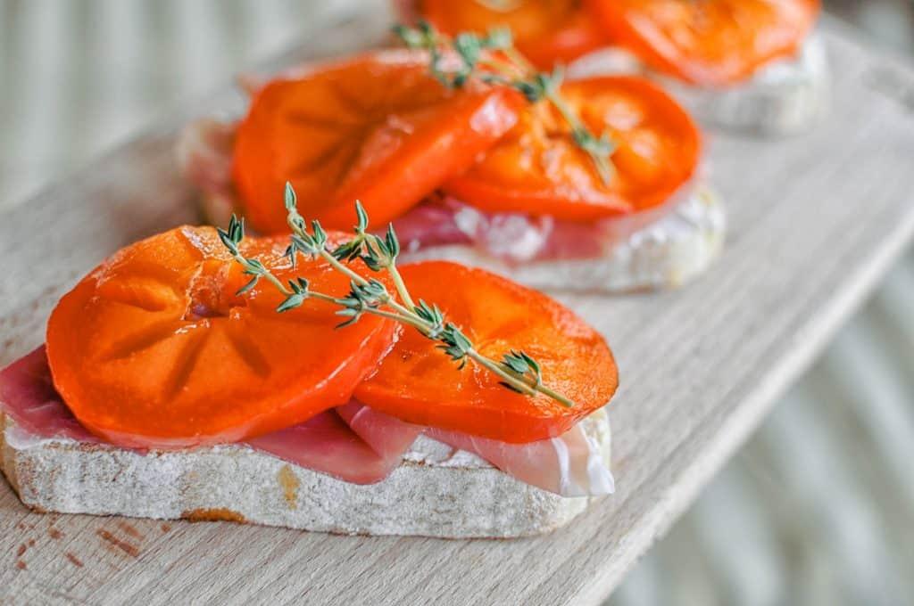 persimmon prosciutto crostinis on a cutting board