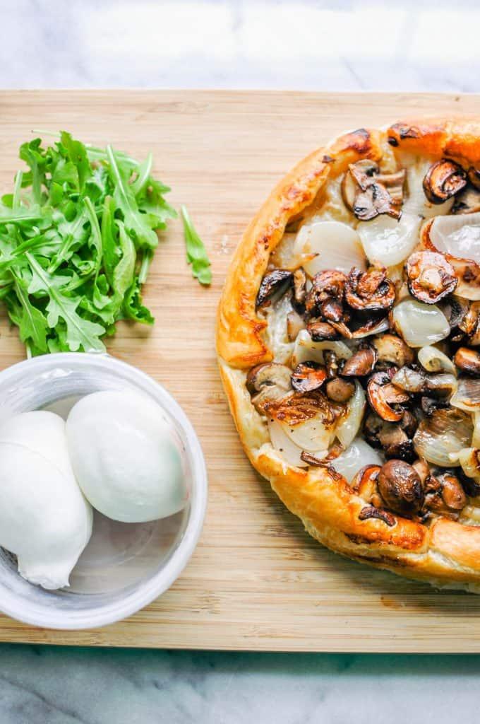 shallot and mushroom tarte tatin on a cutting board with arugula and mozzarella