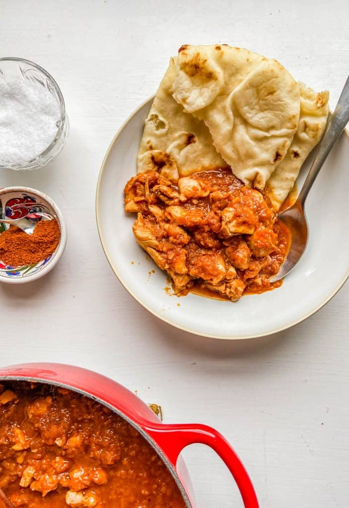 berbere chicken in a bowl with naan