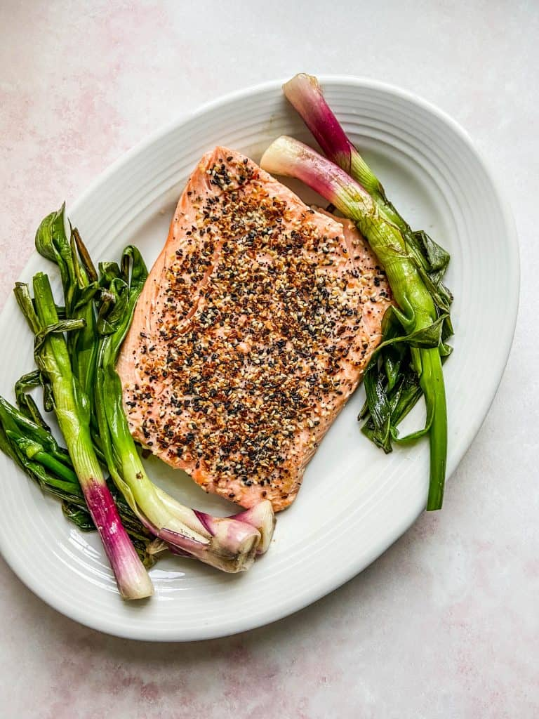 sesame salmon with roasted spring onions on a white serving platter