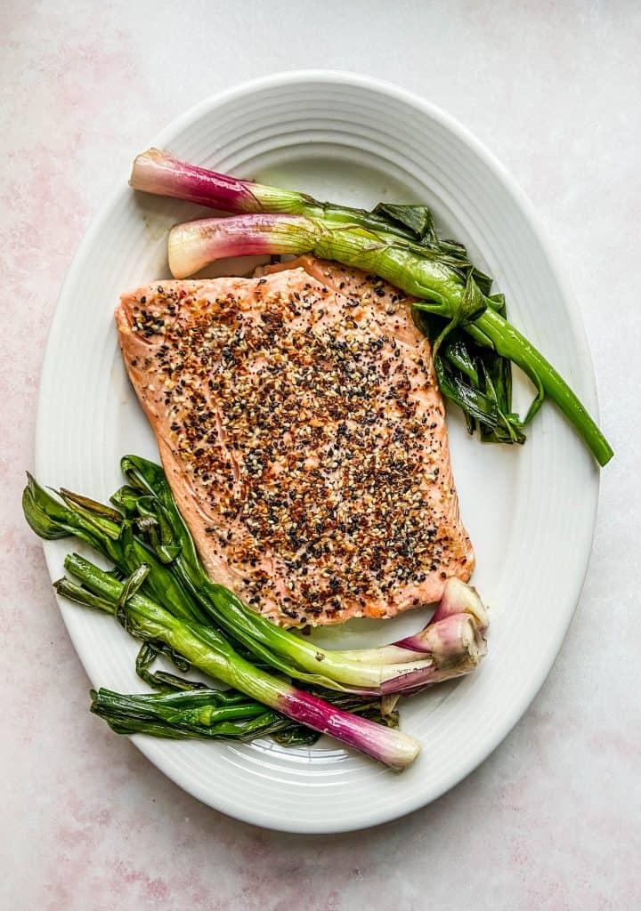 sesame salmon with roasted spring onions on a white platter