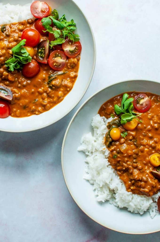 two bowls of coconut lentil curry and white rice, topped with cherry tomatoes and cilantro